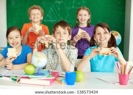 Portrait of cute schoolchildren with sandwiches looking at camera in classroom - stock photo