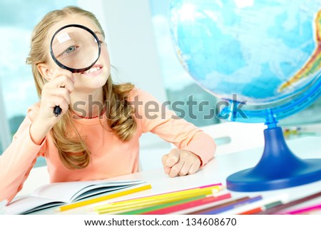 Portrait of cute schoolgirl looking at globe through spy glass - stock photo