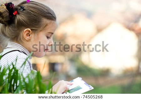 Portrait of cute schoolgirl reading interesting book in natural environment - stock photo