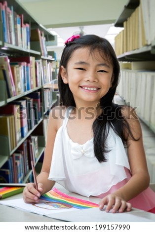 Portrait of cute schoolgirl smiling while drawing a picture in library - stock photo