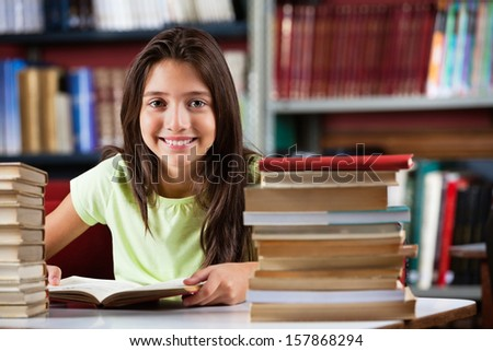Portrait of cute schoolgirl smiling while sitting with stack of books at table in library - stock photo