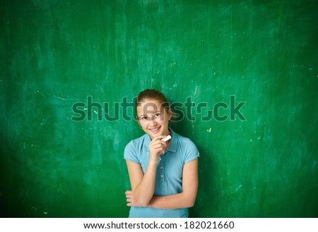 Portrait of cute schoolgirl with piece of chalk looking at camera by the blackboard - stock photo