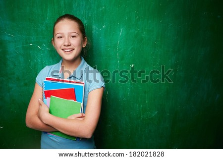 Portrait of cute schoolgirl with textbooks looking at camera by the blackboard - stock photo