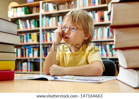 Portrait of cute schoolkid sitting in the library