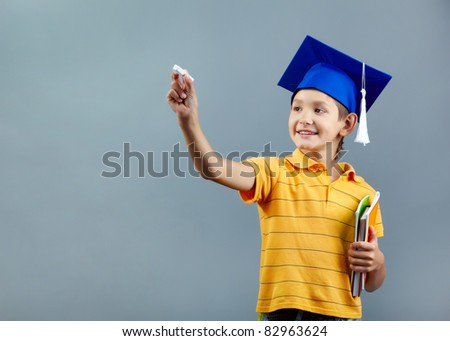 Portrait of cute schoolkid writing with chalk on imaginary blackboard - stock photo
