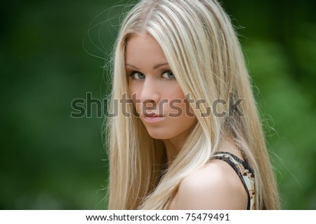 Portrait of cute sexy young blonde girl with long hair, nice makeup and excellent skin posing outdoors with a serious look - stock photo