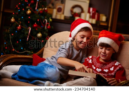 Portrait of cute siblings in Santa caps reading Christmas tales - stock photo