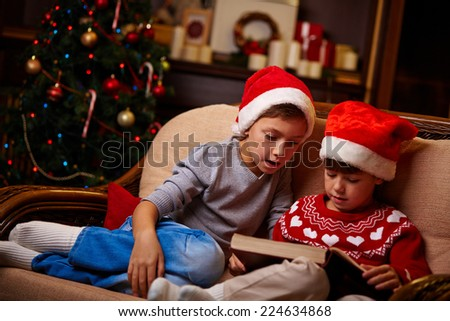 Portrait of cute siblings in Santa caps reading tales on Christmas evening - stock photo