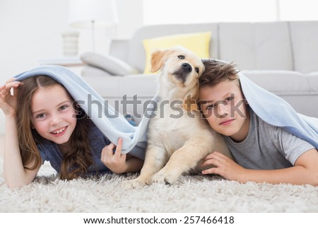 Portrait of cute siblings with dog under blanket in living room - stock photo