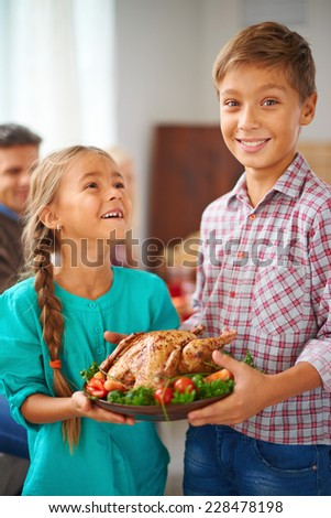 Portrait of cute siblings with roasted turkey garnished with vegetables on plate - stock photo