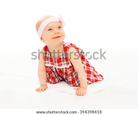 Portrait of cute smiling baby in dress with headband crawls - stock photo