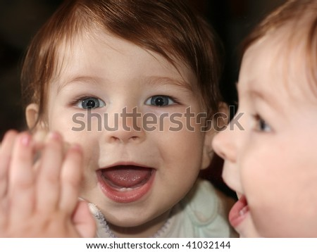 Young woman applying face mask looking into mirror smiling for Mirror twins