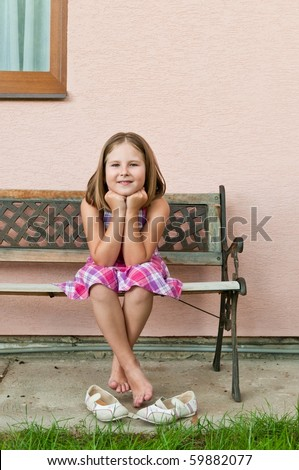 Portrait of cute smiling child sitting on bench - wall in background
