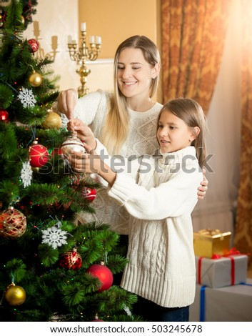 Portrait of cute smiling girl helping mother decorating Christmas tree