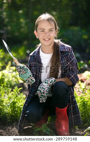 Portrait of cute smiling girl in gloves and gumboots posing at garden