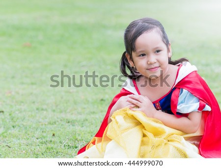 Portrait of cute smiling little girl in princess dress on field background