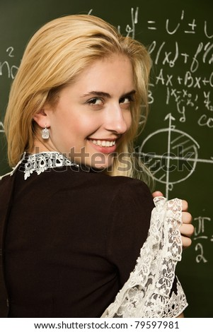 Portrait of cute smiling school girl in a classroom - stock photo