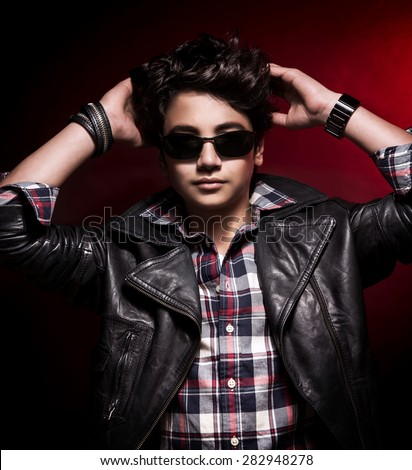 Portrait of cute stylish guy with his hands behind his head over dark red background, wearing fashion clothes and accessories - stock photo