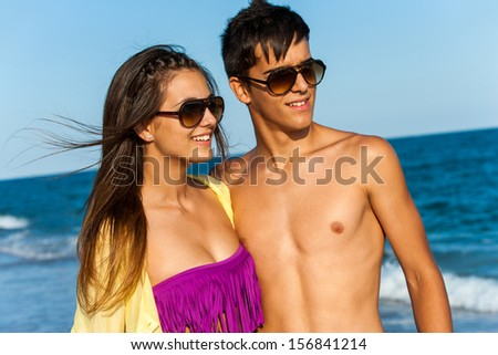 Portrait of cute teen couple standing on beach with sunglasses. - stock photo