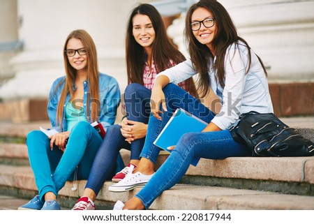 Portrait of cute teen students in casual sitting on stairs of college - stock photo