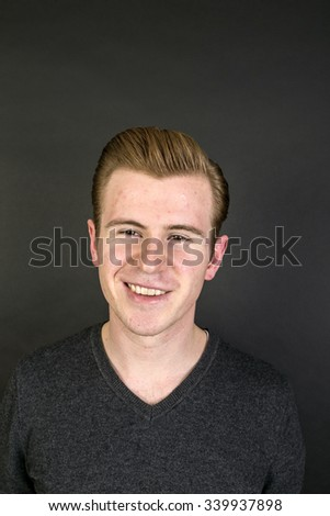 portrait of cute teenage boy with red hair isolated on black