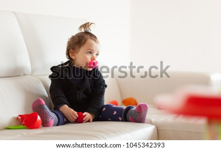 Portrait of cute toddler baby girl playing on the sofa.