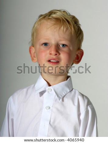Portrait of cute toddler boy dressed up in a white shirt, high-key photograph