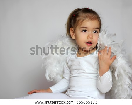 Portrait of cute toddler girl in a white t-shirt with white wings as a Cupid sitting touch wings with hand looking surprised on white background, Saint Valentines Day card, romantic and love concept