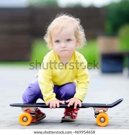 Portrait of cute toddler girl with skateboard outdoors