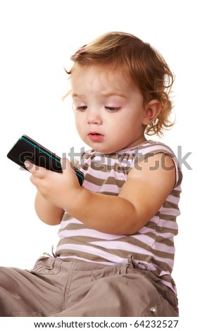 Portrait of cute toddler looking at cellular phone in her hands