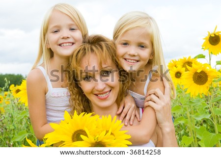 Portrait of cute twins embracing their mother with smiles in sunflower field - stock photo