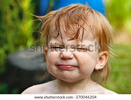 Portrait of cute wet little girl with happy emotions on her face and narrowing her eyes with pleasure after taking a rain shower outdoors.