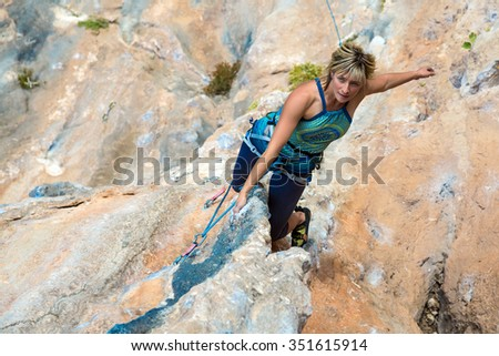 Portrait of Cute Woman doing Exercise climb natural rock preparing for next Move Top View - stock photo