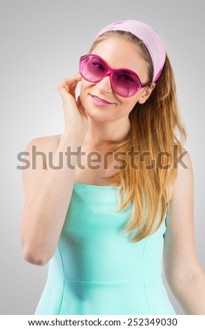Portrait of cute woman wearing rose-colored sunglasses - stock photo