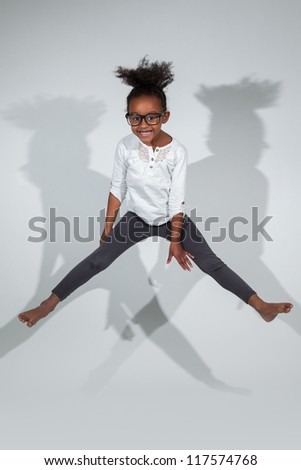 Portrait of cute Young African American girl jumping, over gray background
