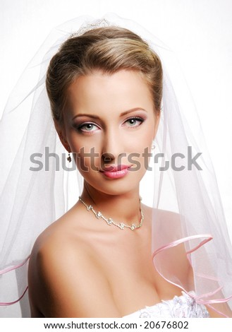Portrait of cute young bride wearing the white vial. Fashion wedding shot on a white