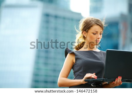 Portrait of cute young business woman near office building with laptop - stock photo