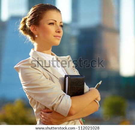 Portrait of cute young business woman outdoor over building background - stock photo