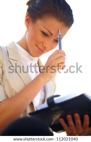 Portrait of cute young business woman outdoor researching notebook