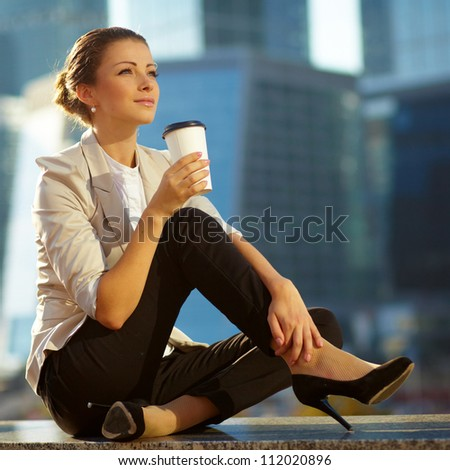 Portrait of cute young business woman outdoor with coffee cup