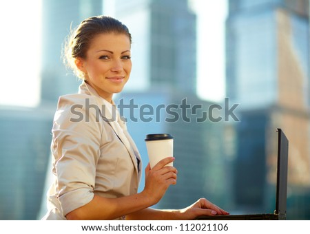 Portrait of cute young business woman outdoorwith coffee and laptop