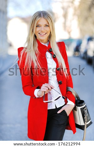 Portrait of cute young business woman smiling outdoors - stock photo