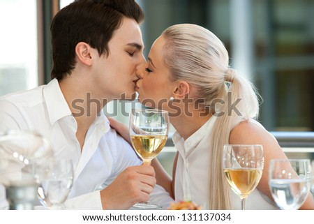 Portrait of cute young couple kissing at dinner table. - stock photo