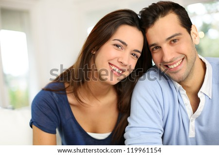 Portrait of cute young couple sitting in sofa - stock photo