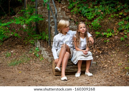 Portrait of cute young couple sitting on log in woods.