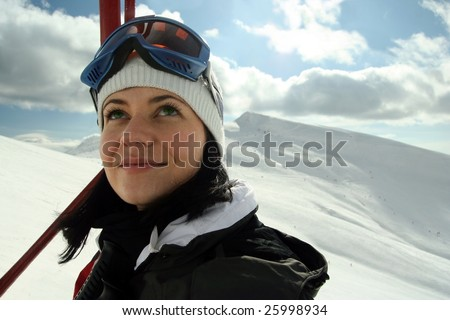 Portrait of cute young female in chair lift ,after skiing, looking at sky. - stock photo