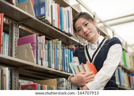 Portrait of cute young female student holding a stack of books next to a bookshelf in library