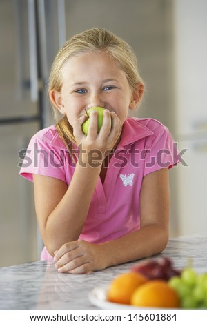 Portrait of cute young girl eating green apple at kitchen counter - stock photo
