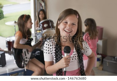 Portrait of cute young girl singing into microphone with friends playing musical instrument in garage - stock photo