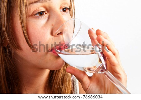 portrait of cute young teenage girl drinking out of a glass
